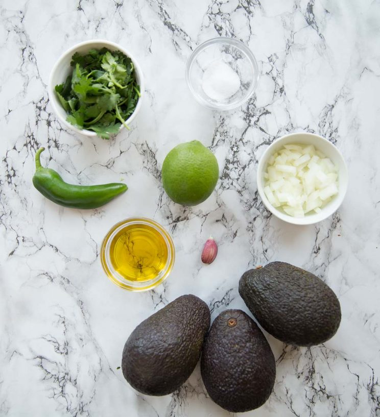 overhead shot of guacamole ingredients on marble background