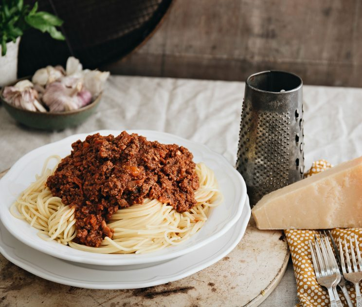 closeup shot of bolognese on spaghetti with parmesan next to it