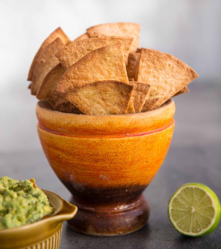 Homemade Baked Tortilla Chips in a pot with guac and lime in the background