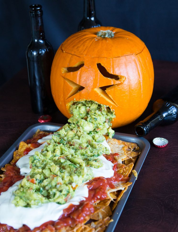 Pumpkin throwing up guacamole over nachos
