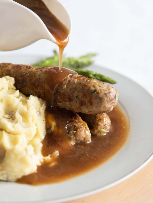 pouring gravy over sausages on white plate with asparagus and mash