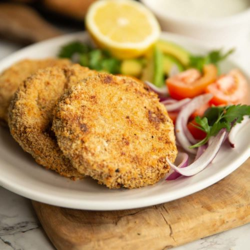 tuna patties plated with salad on white plate with dip and more patties blurred in background