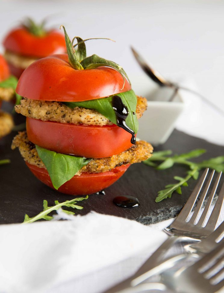 Stacked Tomato and Fried Mozzarella Salad with Balsamic Glaze dripping down the basil leaf