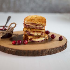 3 grilled cheese stacked on each other on wooden board with glass pot of cranberry sauce by the side