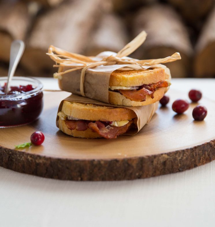 brie toasties stacked on wooden board wrapped in paper parcels with string bow