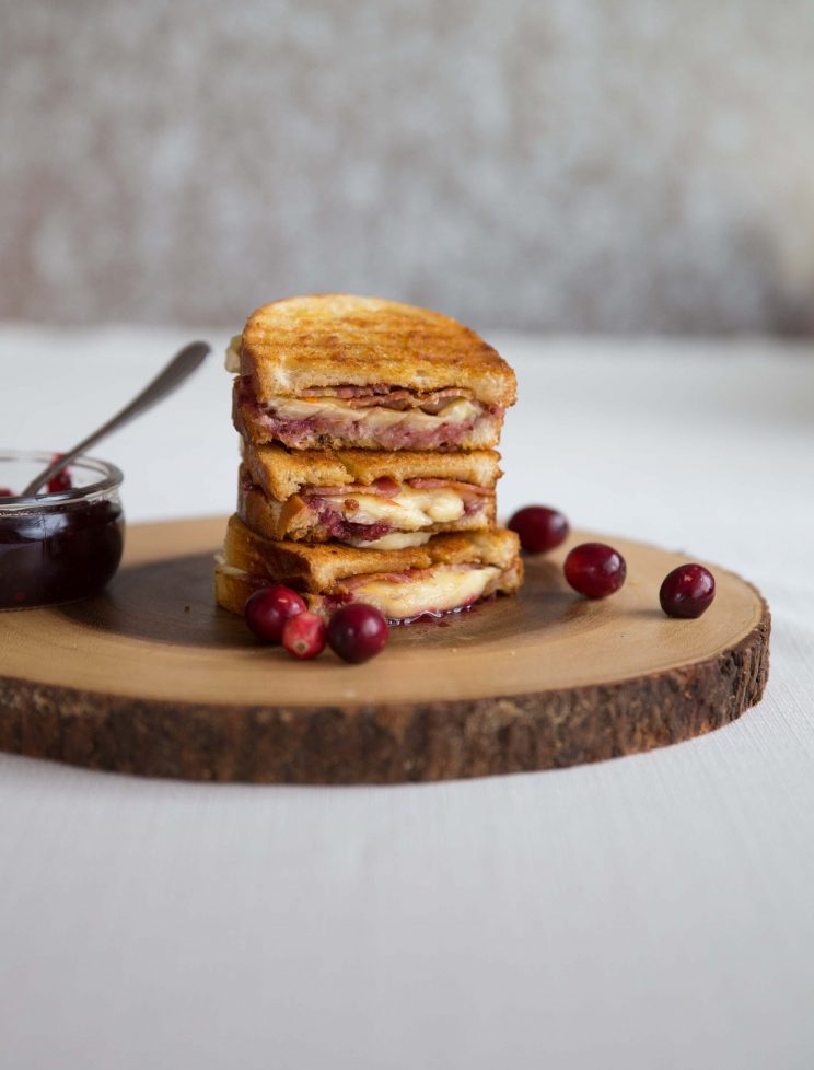 Cranberry Bacon Brie Grilled Cheese stacked on top of each other on wooden block