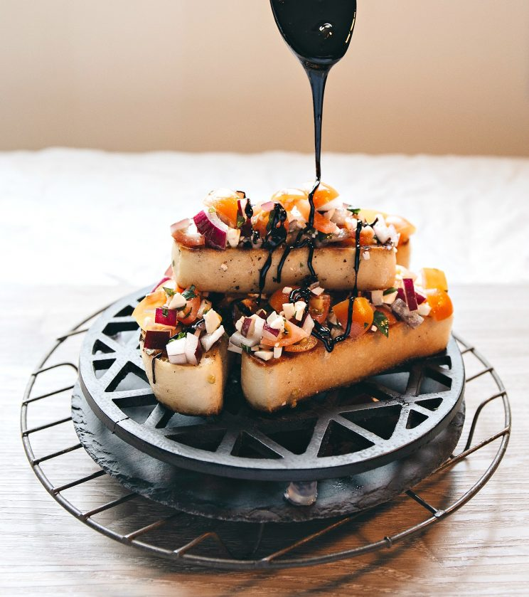 Feta Bruschetta with Balsamic Glaze - pouring over glaze