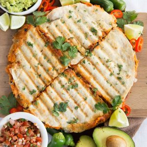 overhead shot of quesadillas sliced into 4 garnished with chilli, jalapeno and coriander