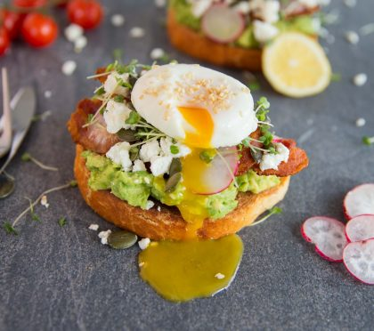 Cafe style smashed avocado on toast Yolk dripping down