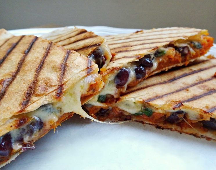 closeup shot of quesadillas cut open showing filling and cheese pull