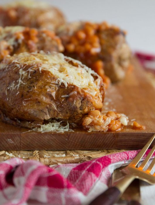 baked potato with beans pouring out on chopping board with 3 more blurred in the background