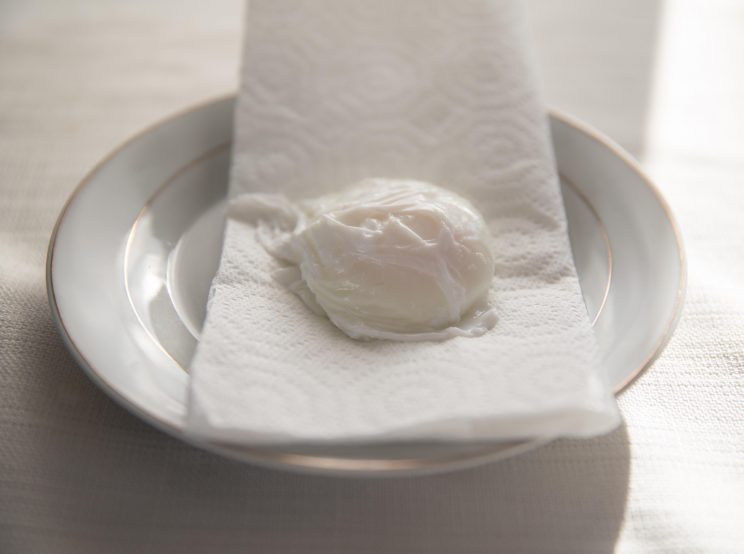 resting poached egg on paper towel
