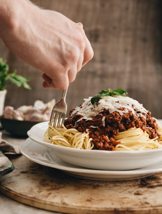 twisting fork into spaghetti bolognese in white bowl