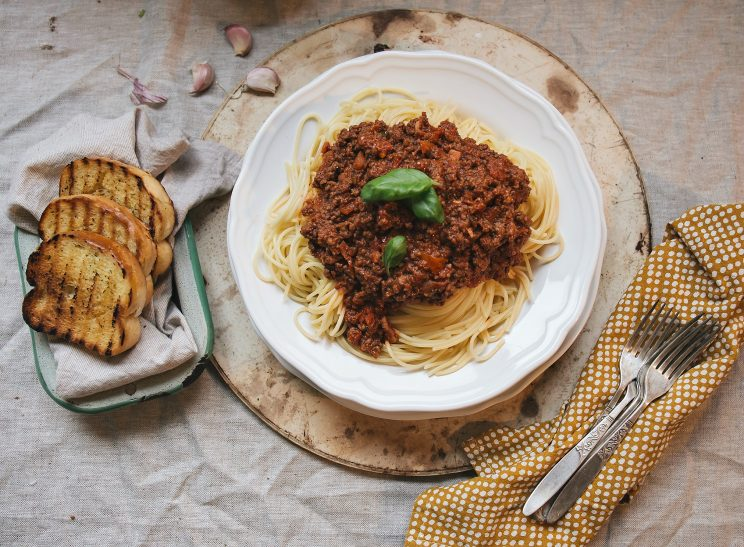 The Best Spaghetti Bolognese Recipe - overhead shot with garlic bread and forks