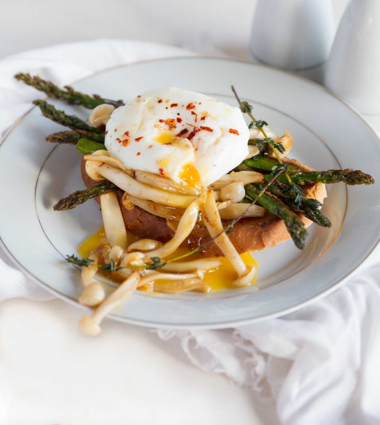 closeup shot of poached egg on toast with asparagus