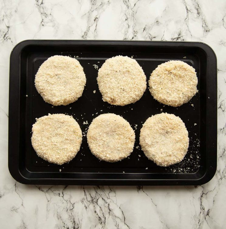 overhead shot of tuna patties on black baking tray ready to go in oven