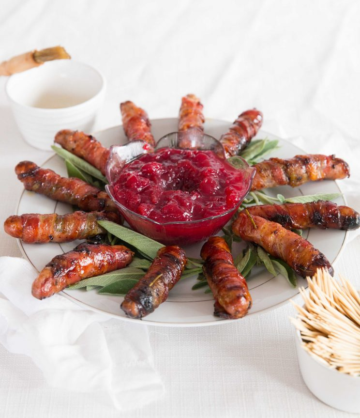 pigs in blankets circled around cranberry sauce on sage