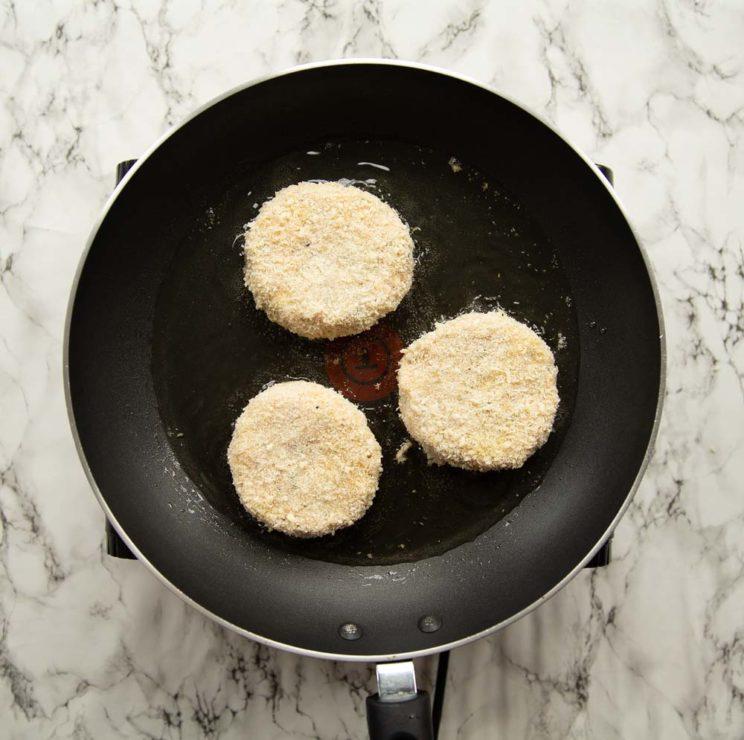 overhead shot of 3 patties frying in a skillet