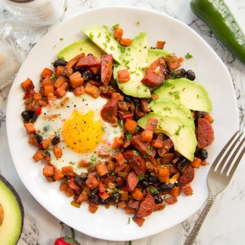 overhead shot of Sweet Potato Breakfast Hash on white plate served with avocado slices