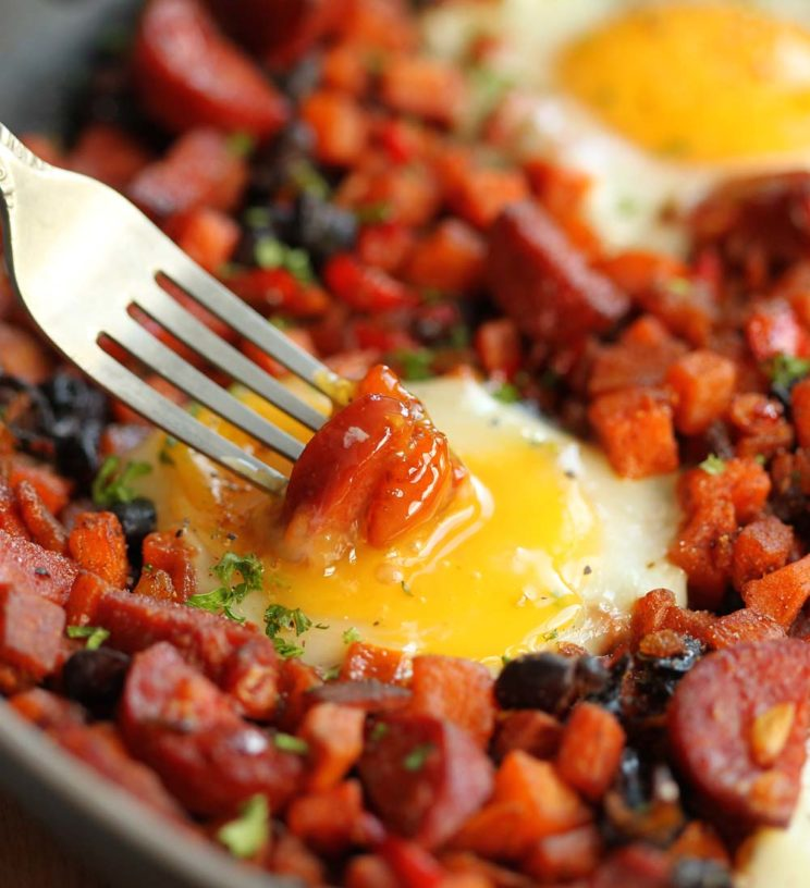 dipping chorizo into egg yolk in skillet