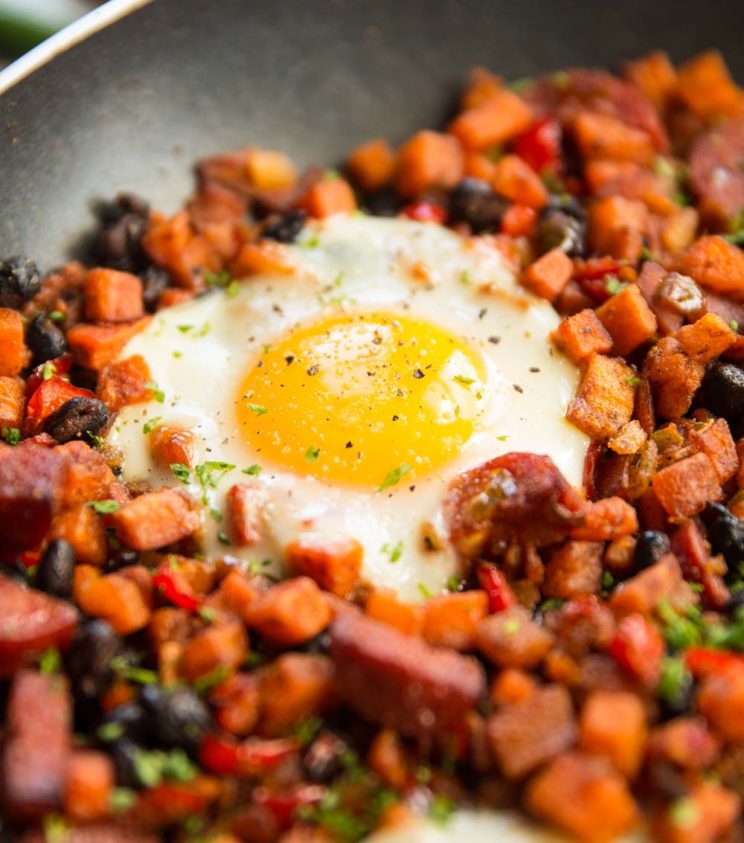 closeup shot of egg in sweet potato hash skillet