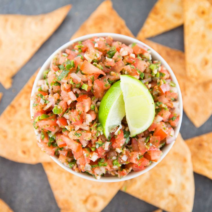 overhead shot of salsa in bowl with lime wedges and tortilla chips