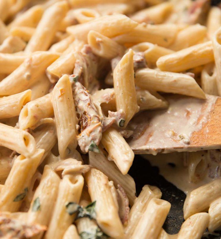 closeup shot of wooden spoon diving into skillet of creamy pasta