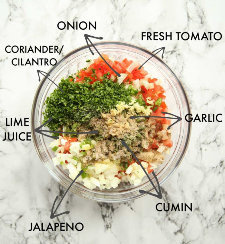 overhead shot of salsa ingredients in glass bowl with labels