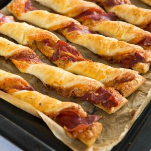 row of cheese and prosciutto twists on black tray fresh out the oven