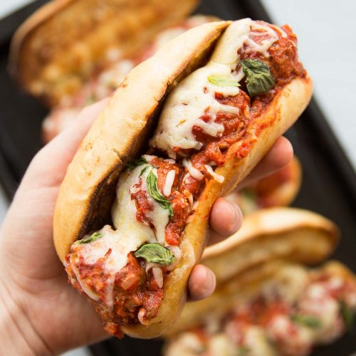 closeup shot of a hand holding meatball sub with melted cheese and 3 subs in the background
