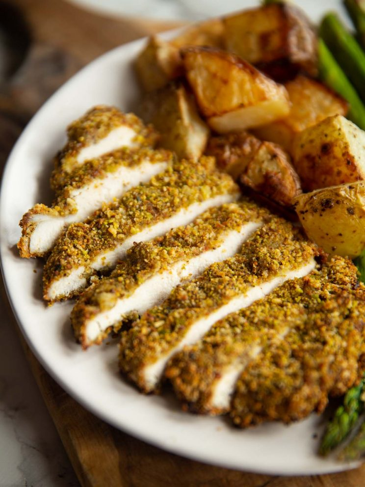 sliced pistachio crusted chicken on small white plate with roast potatoes and asparagus