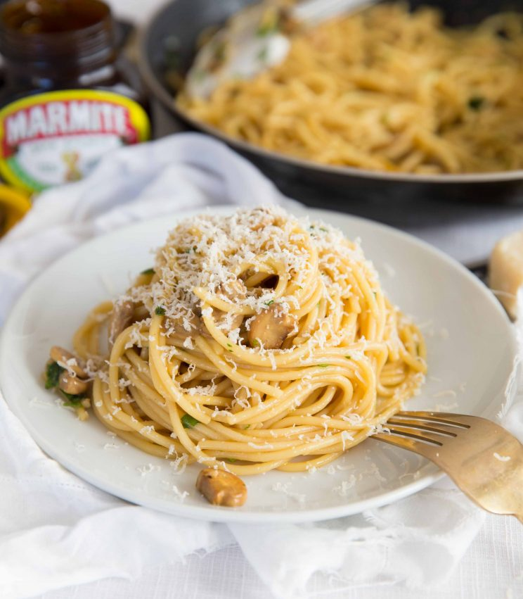 Marmite Pasta sprinkled with Parmesan Cheese with Jar of Marmite in the background