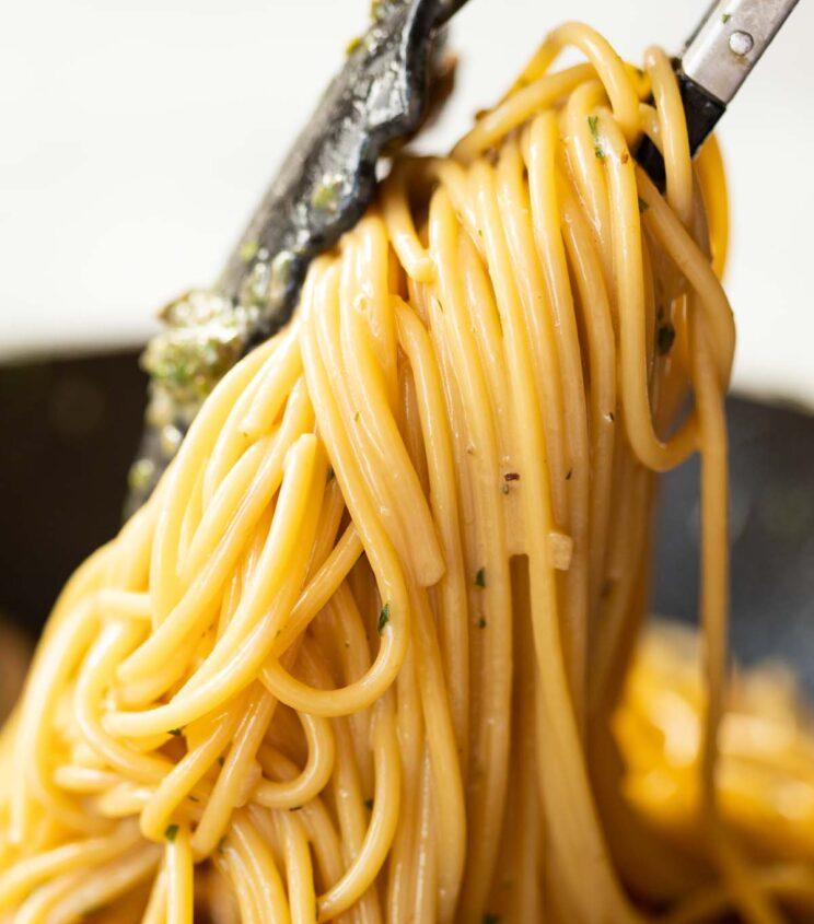 close up shot of pasta tongs lifting up spaghetti from pan