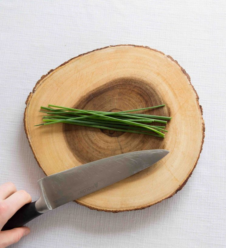 wooden board with fresh chives and sharp knife