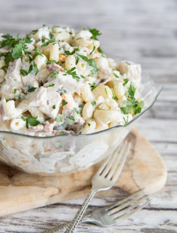Chicken Bacon Ranch Pasta Salad with fresh parsley in a glass bowl