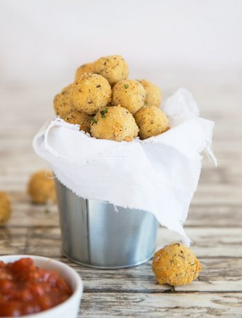 cheese balls served in a tin bucket with marinara dip blurred in the front