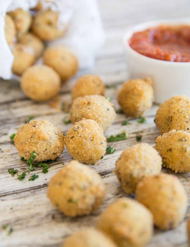 cheese balls scattered across surface with pot of marinara dip blurred in background