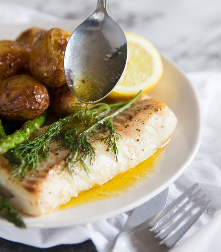 Pan fried cod with brown butter sauce dripping off spoon