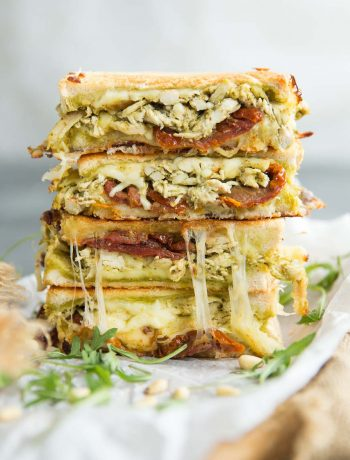 2 sandwiches stacked on each other garnished with arugula and pine nuts