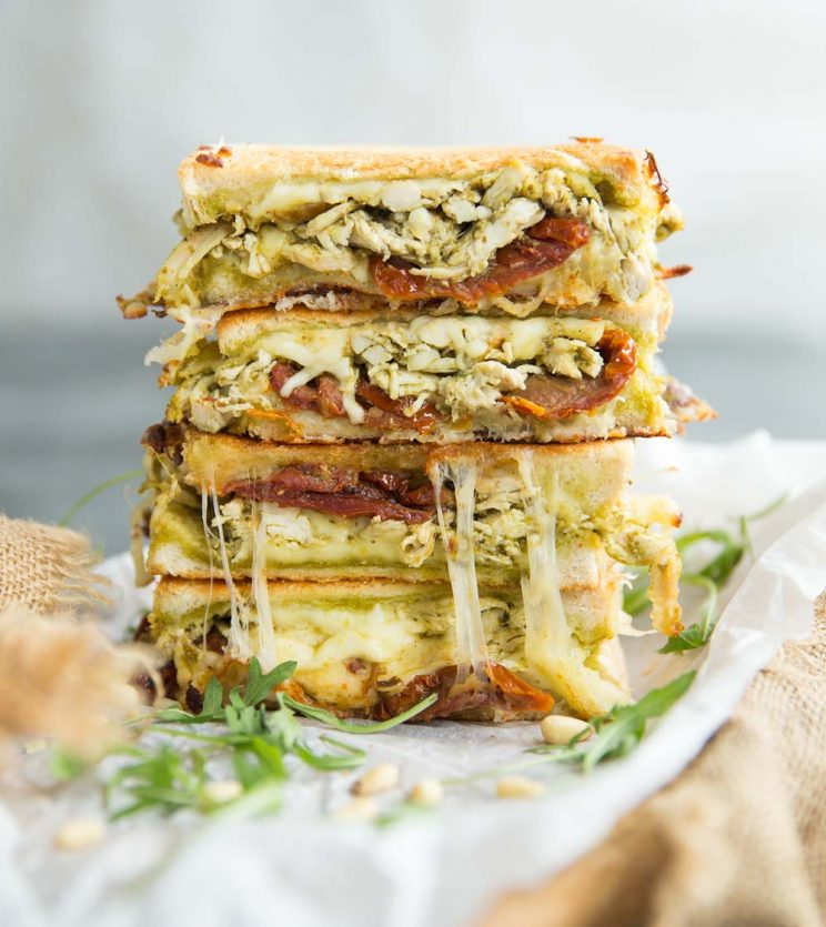 4 slices of Chicken Pesto Grilled Cheese stacked on eachother garnished with arugula and pinenuts
