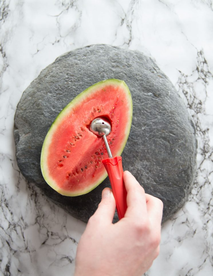hand using melon baller to cut into 1/4 whole watermelon