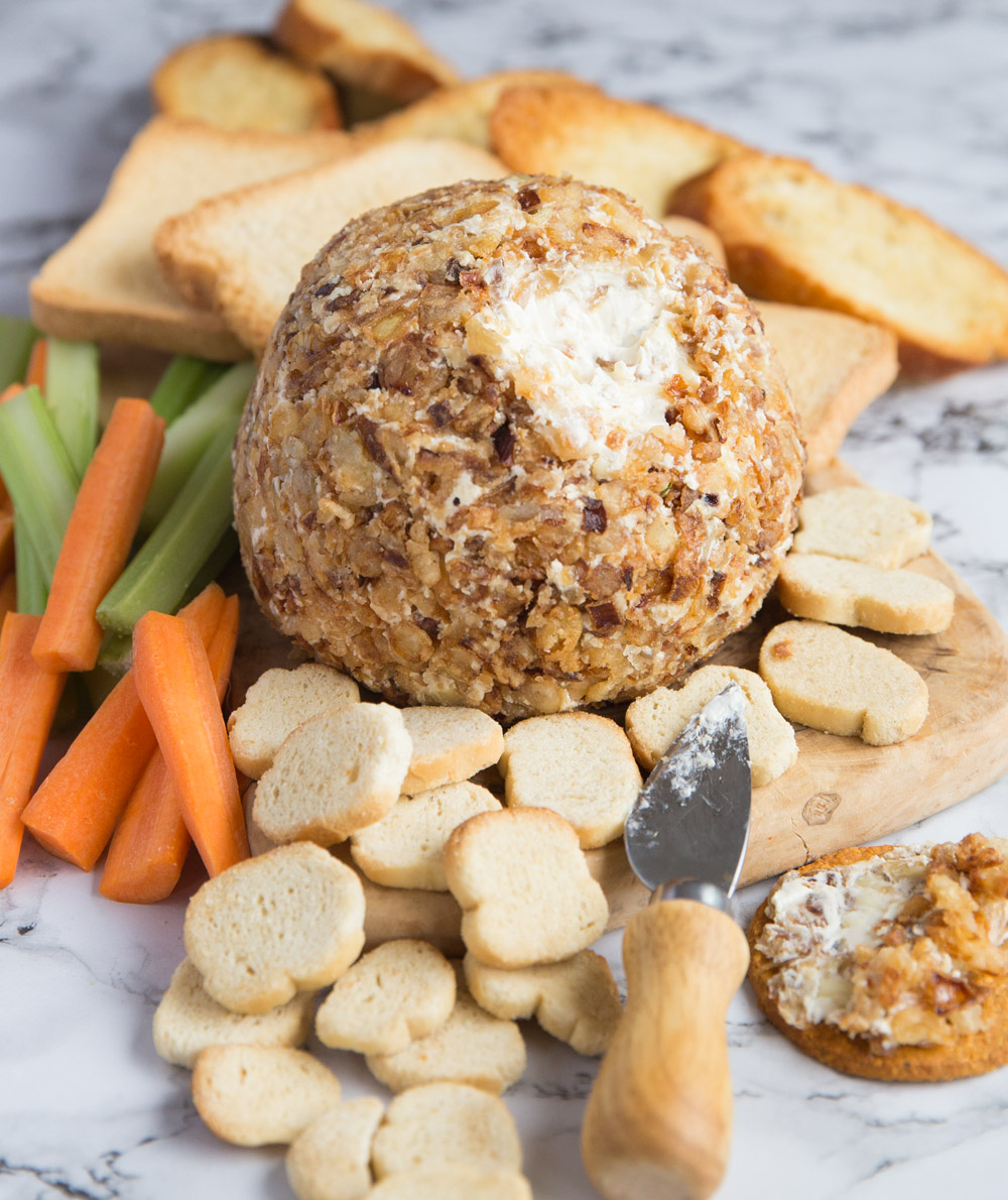 cream cheese ball coated in crispy fried onions on chopping board with biscuits and bread