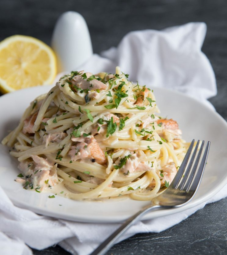 close up shot of salmon pasta on white plate garnished with parsley