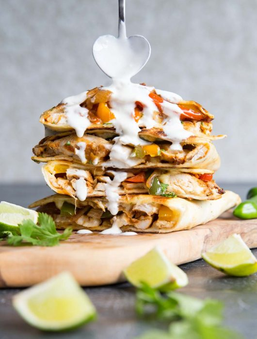 quesadillas stacked on each other with heart shaped spoon pouring over sour cream