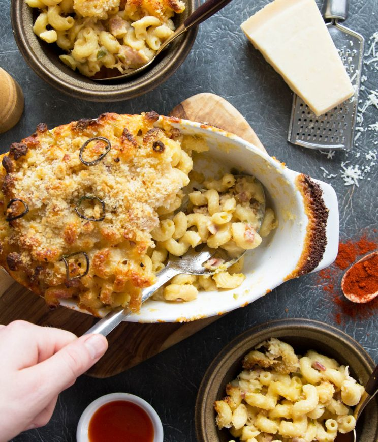 overhead shot of spicy mac and cheese in baking dish with props scattered around