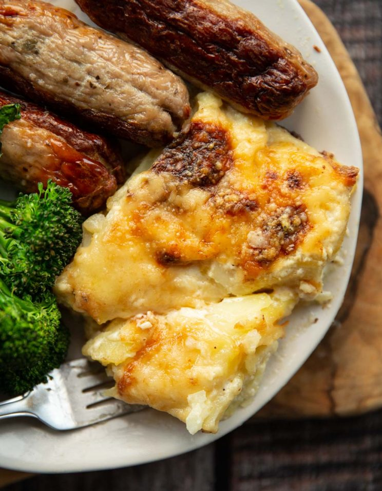 overhead shot of dauphinoise served on plate with sausages and broccolini