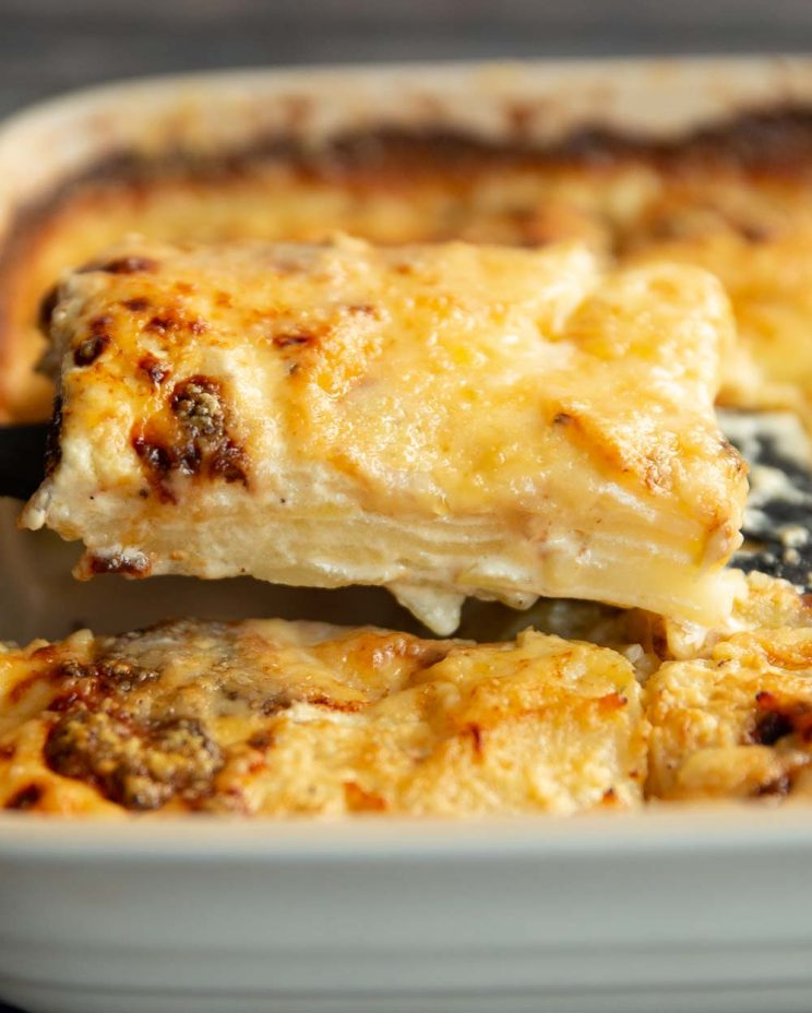 close up shot of dauphinoise being scooped from baking dish