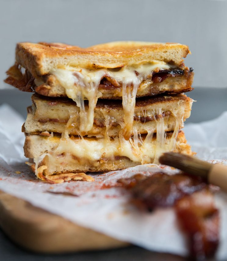 Maple glazed bacon grilled cheese sandwich with maple bacon in the corner
