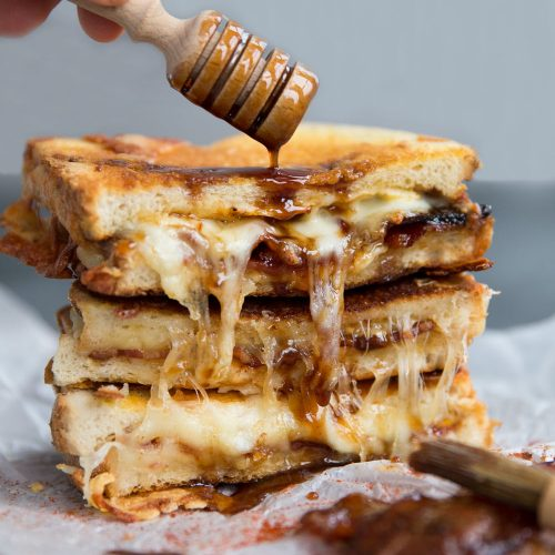 Maple Bacon Grilled Cheese with honey dipping pouring over sauce