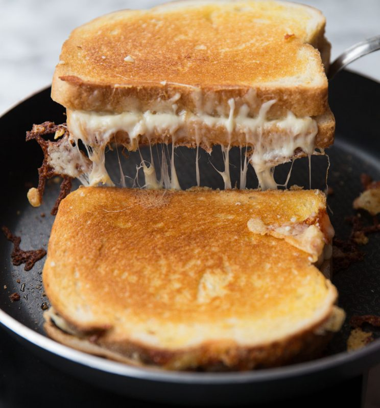 maple bacon grilled cheese frying in the pan with cheese pull